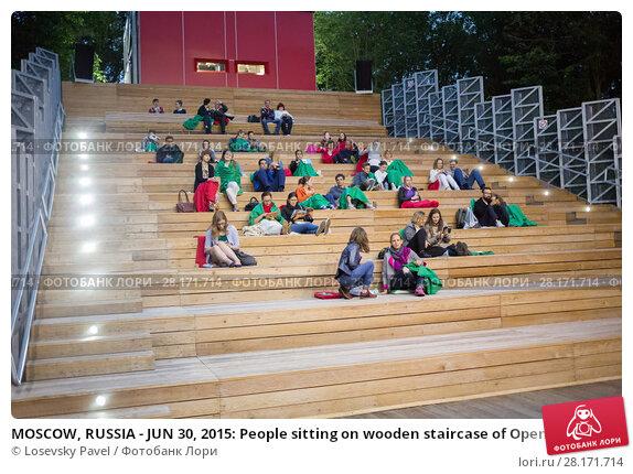 Купить «MOSCOW, RUSSIA - JUN 30, 2015: People sitting on wooden staircase of Open Air Cinema in Sokolniki», фото № 28171714, снято 30 июня 2015 г. (c) Losevsky Pavel / Фотобанк Лори