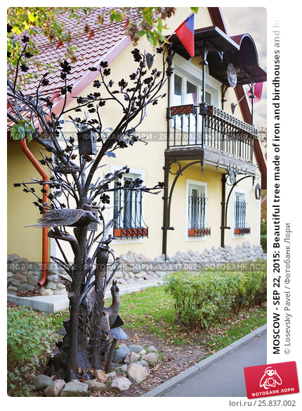 Купить «MOSCOW - SEP 22, 2015: Beautiful tree made of iron and birdhouses and birds near cottage in VDNH», фото № 25837002, снято 22 сентября 2015 г. (c) Losevsky Pavel / Фотобанк Лори