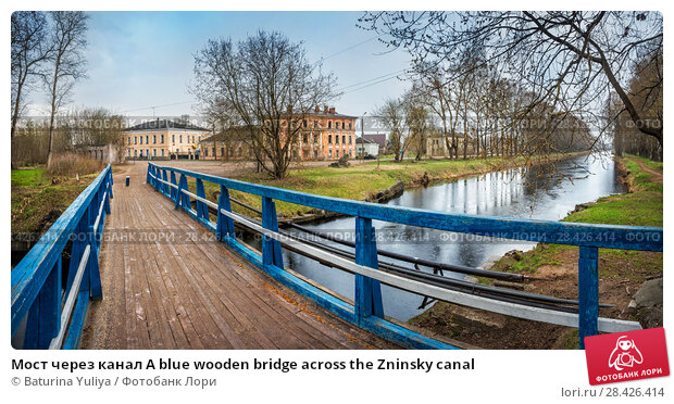 Купить «Мост через канал A blue wooden bridge across the Zninsky canal», фото № 28426414, снято 1 мая 2018 г. (c) Baturina Yuliya / Фотобанк Лори