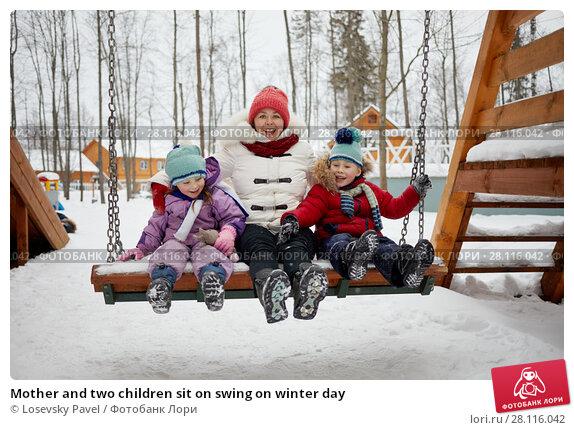 Купить «Mother and two children sit on swing on winter day», фото № 28116042, снято 4 февраля 2017 г. (c) Losevsky Pavel / Фотобанк Лори