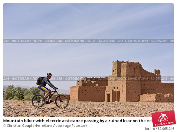 Mountain biker with electric assistance passing by a ruined ksar on the edge of a track through the reg, between Agdz and Zagora, Draa River valley, Province... (2019 год). Редакционное фото, фотограф Christian Goupi / age Fotostock / Фотобанк Лори