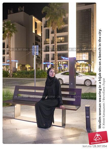 Купить «Muslim woman wearing in a hijab sits on a bench in the city.», фото № 28307054, снято 25 марта 2018 г. (c) Женя Канашкин / Фотобанк Лори