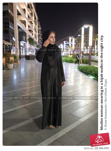 Купить «Muslim woman wearing in a hijab walks in the night city.», фото № 28306474, снято 25 марта 2018 г. (c) Женя Канашкин / Фотобанк Лори