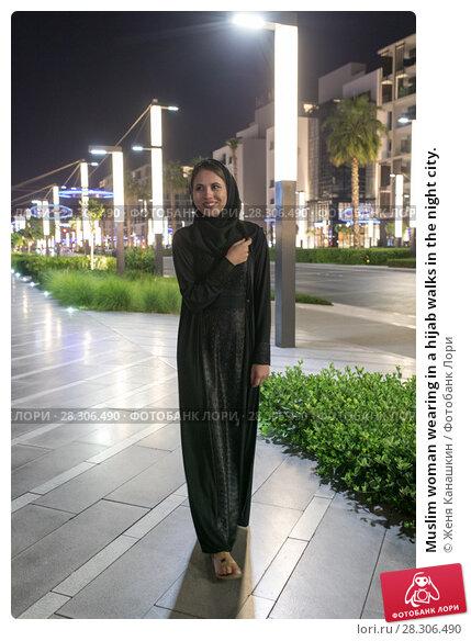 Купить «Muslim woman wearing in a hijab walks in the night city.», фото № 28306490, снято 25 марта 2018 г. (c) Женя Канашкин / Фотобанк Лори