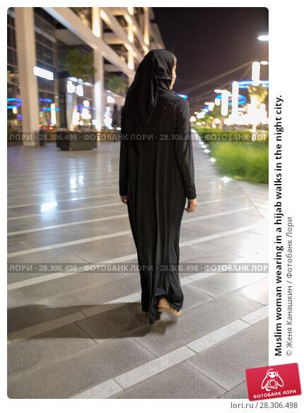 Купить «Muslim woman wearing in a hijab walks in the night city.», фото № 28306498, снято 25 марта 2018 г. (c) Женя Канашкин / Фотобанк Лори