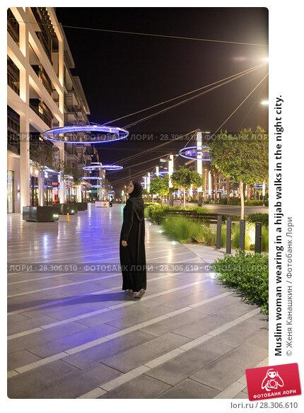 Купить «Muslim woman wearing in a hijab walks in the night city.», фото № 28306610, снято 25 марта 2018 г. (c) Женя Канашкин / Фотобанк Лори