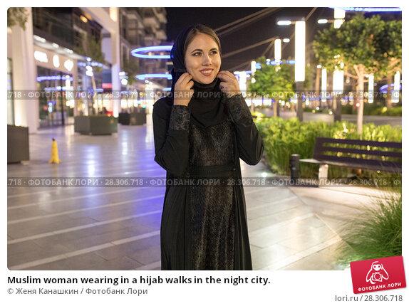Купить «Muslim woman wearing in a hijab walks in the night city.», фото № 28306718, снято 25 марта 2018 г. (c) Женя Канашкин / Фотобанк Лори
