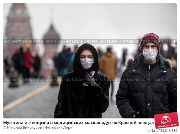Купить «Мужчина и женщина в медицинских масках идут по Красной площади в городе Москве во время эпидемии гриппа, Россия», фото № 33018330, снято 1 февраля 2020 г. (c) Николай Винокуров / Фотобанк Лори