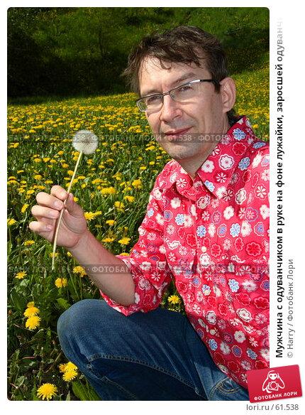 Мужчина с одуванчиком в руке на фоне лужайки, заросшей одуванчиками, фото № 61538, снято 23 мая 2006 г. (c) Harry / Фотобанк Лори
