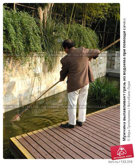 Мужчина вылавливает грязь из водоема при помощи сачка, фото № 133318, снято 25 сентября 2017 г. (c) Вера Тропынина / Фотобанк Лори