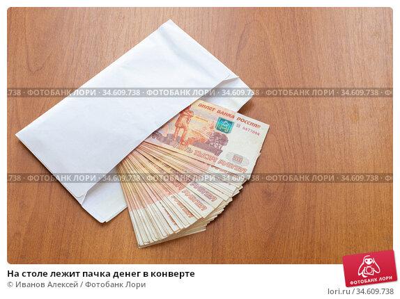 На столе лежит пачка денег в конверте. Стоковое фото, фотограф Иванов Алексей / Фотобанк Лори