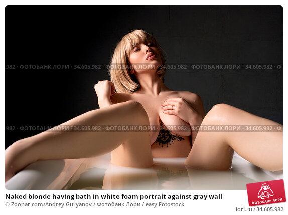 Naked blonde having bath in white foam portrait against gray wall. Стоковое фото, фотограф Zoonar.com/Andrey Guryanov / easy Fotostock / Фотобанк Лори