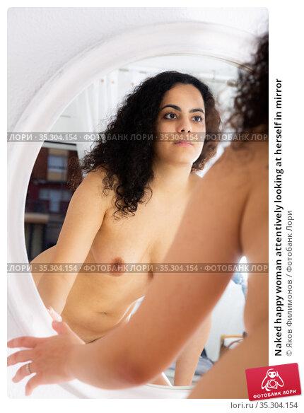 Naked happy woman attentively looking at herself in mirror. Стоковое фото, фотограф Яков Филимонов / Фотобанк Лори
