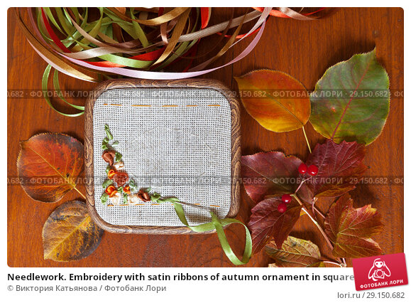 Купить «Needlework. Embroidery with satin ribbons of autumn ornament in square hoop on a wooden table and fallen leaves (These pictures of embroidery and embroidery with satin ribbons were performed by the author of the images)», фото № 29150682, снято 27 сентября 2018 г. (c) Виктория Катьянова / Фотобанк Лори