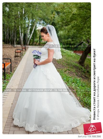 Купить «Невеста стоит на дороге и смотрит на букет», эксклюзивное фото № 19168566, снято 13 сентября 2015 г. (c) Игорь Низов / Фотобанк Лори