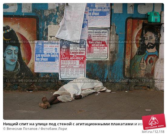 Нищий спит на улице под стеной с агитационными плакатами и изображениями святых, фото № 12118, снято 7 декабря 2004 г. (c) Вячеслав Потапов / Фотобанк Лори