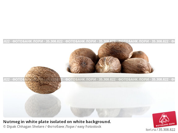 Nutmeg in white plate isolated on white background. Стоковое фото, фотограф Dipak Chhagan Shelare / easy Fotostock / Фотобанк Лори