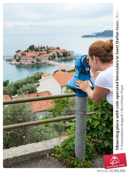 Купить «Observing place with coin operated binoculars in Sveti Stefan town. Woman looking at island in Adriatic sea, Montenegro, Europe», фото № 29382846, снято 3 июня 2016 г. (c) Кекяляйнен Андрей / Фотобанк Лори