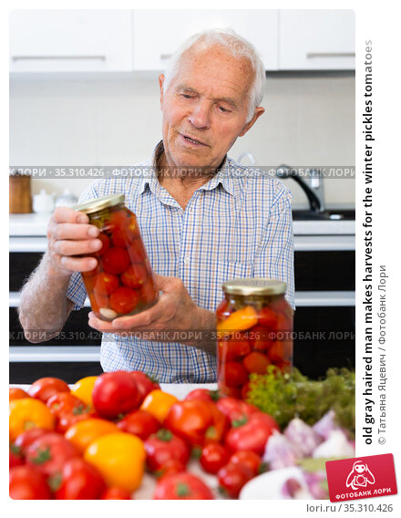 old gray haired man makes harvests for the winter pickles tomatoes. Стоковое фото, фотограф Татьяна Яцевич / Фотобанк Лори
