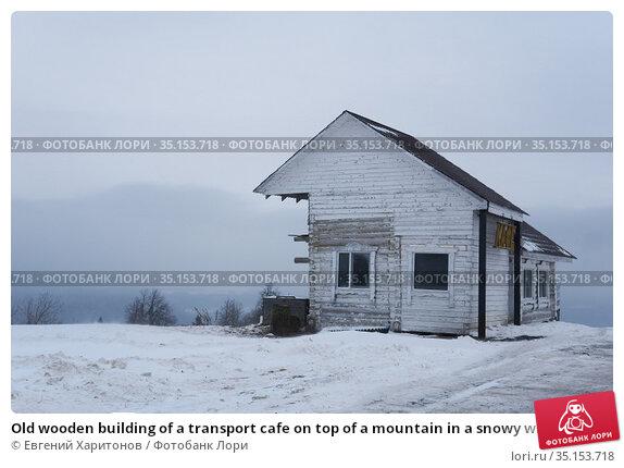 Old wooden building of a transport cafe on top of a mountain in a snowy winter landscape in Perm Krai, Russia. Редакционное фото, фотограф Евгений Харитонов / Фотобанк Лори
