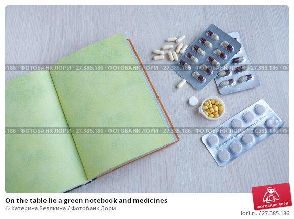 Купить «On the table lie a green notebook and medicines», фото № 27385186, снято 6 января 2018 г. (c) Катерина Белякина / Фотобанк Лори