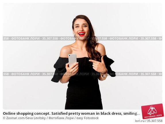 Online shopping concept. Satisfied pretty woman in black dress, smiling... Стоковое фото, фотограф Zoonar.com/Seva Levitsky / easy Fotostock / Фотобанк Лори