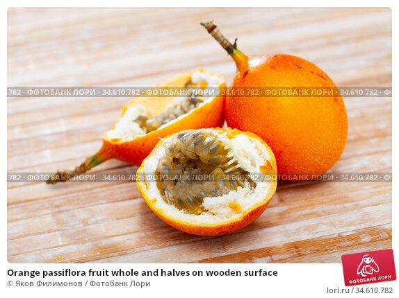 Orange passiflora fruit whole and halves on wooden surface. Стоковое фото, фотограф Яков Филимонов / Фотобанк Лори