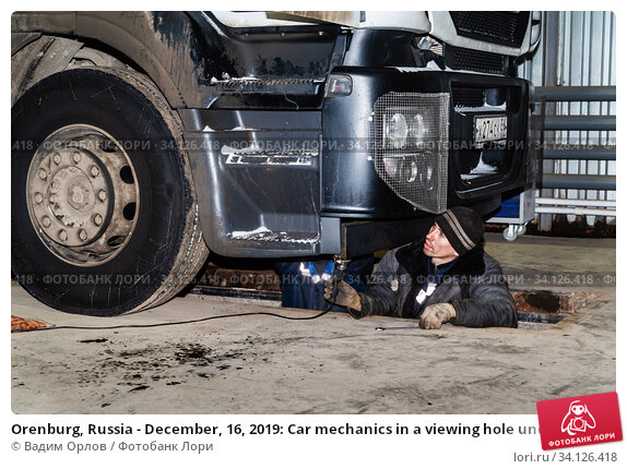 Купить «Orenburg, Russia - December, 16, 2019: Car mechanics in a viewing hole under a truck», фото № 34126418, снято 16 декабря 2019 г. (c) Вадим Орлов / Фотобанк Лори