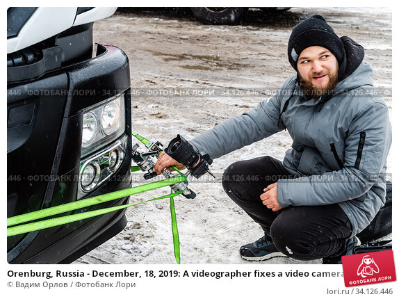 Купить «Orenburg, Russia - December, 18, 2019: A videographer fixes a video camera on a bumper of a truck, winter», фото № 34126446, снято 18 декабря 2019 г. (c) Вадим Орлов / Фотобанк Лори
