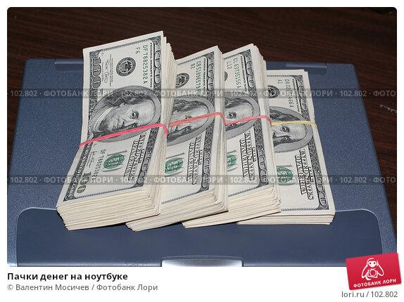 Пачки денег на ноутбуке, фото № 102802, снято 26 апреля 2017 г. (c) Валентин Мосичев / Фотобанк Лори