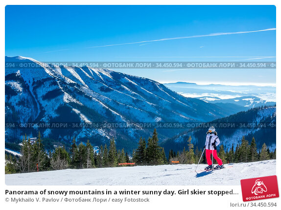 Panorama of snowy mountains in a winter sunny day. Girl skier stopped... Стоковое фото, фотограф Mykhailo V. Pavlov / easy Fotostock / Фотобанк Лори