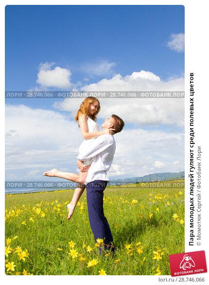Купить «Пара молодых людей гуляют среди полевых цветов», фото № 28746066, снято 25 июня 2018 г. (c) Момотюк Сергей / Фотобанк Лори