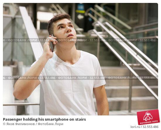 Купить «Passenger holding his smartphone on stairs», фото № 32553486, снято 24 августа 2018 г. (c) Яков Филимонов / Фотобанк Лори