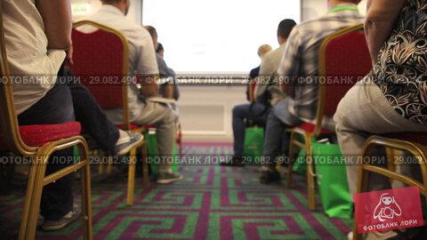 Купить «People on their seats listening and writing at business conference», видеоролик № 29082490, снято 23 сентября 2018 г. (c) Константин Шишкин / Фотобанк Лори