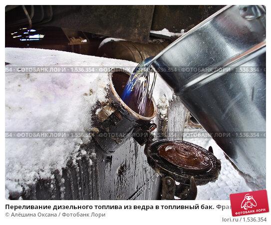 Купить «Переливание дизельного топлива из ведра в топливный бак. Фрагмент», эксклюзивное фото № 1536354, снято 20 февраля 2010 г. (c) Алёшина Оксана / Фотобанк Лори