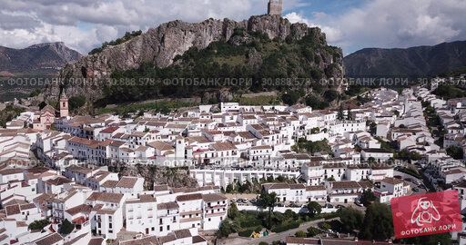 Купить «Picturesque aerial view of Zahara de la Sierra with ancient castle on rocky hill against backdrop of lake, Spain», видеоролик № 30888578, снято 18 апреля 2019 г. (c) Яков Филимонов / Фотобанк Лори