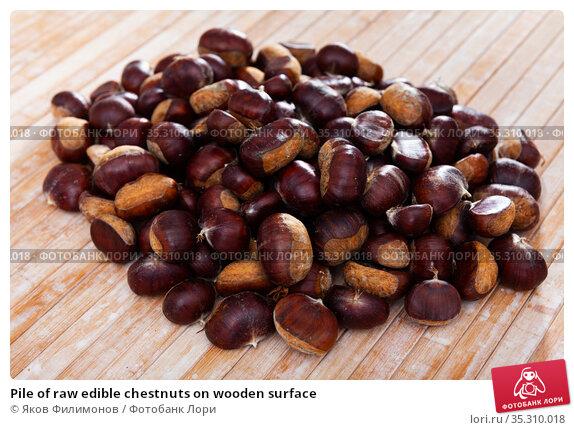 Pile of raw edible chestnuts on wooden surface. Стоковое фото, фотограф Яков Филимонов / Фотобанк Лори