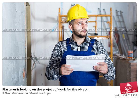 Купить «Plasterer is looking on the project of work for the object.», фото № 32027226, снято 3 июня 2017 г. (c) Яков Филимонов / Фотобанк Лори