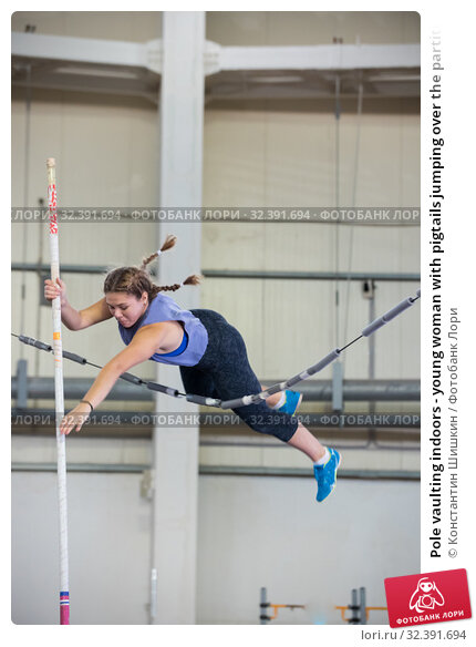 Купить «Pole vaulting indoors - young woman with pigtails jumping over the partition trying not to touching it», фото № 32391694, снято 1 ноября 2019 г. (c) Константин Шишкин / Фотобанк Лори