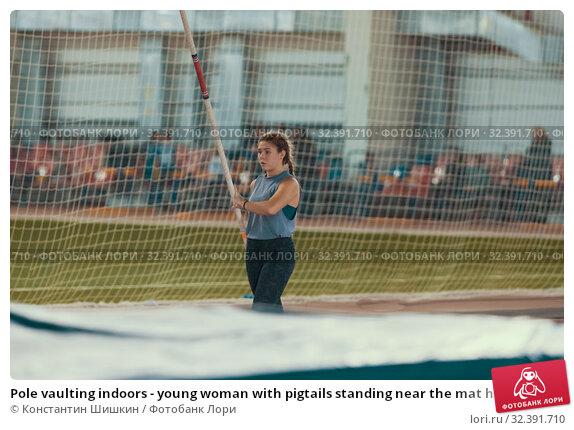Купить «Pole vaulting indoors - young woman with pigtails standing near the mat holding a pole», фото № 32391710, снято 1 ноября 2019 г. (c) Константин Шишкин / Фотобанк Лори