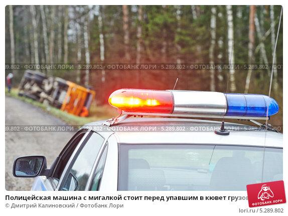 Купить «Полицейская машина с мигалкой стоит перед упавшим в кювет грузовым автомобилем с прицепом», фото № 5289802, снято 16 ноября 2013 г. (c) Дмитрий Калиновский / Фотобанк Лори