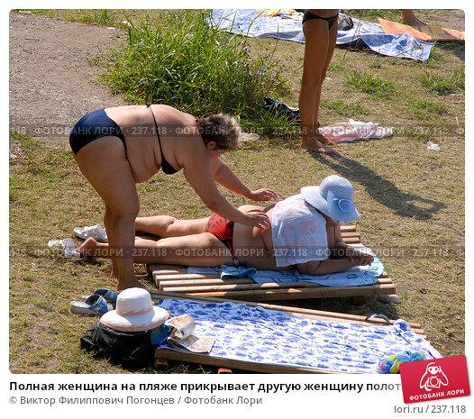 Полная женщина на пляже прикрывает другую женщину полотенцем от палящих лучей солнца. Абхазия. Гагры., фото № 237118, снято 30 августа 2006 г. (c) Виктор Филиппович Погонцев / Фотобанк Лори
