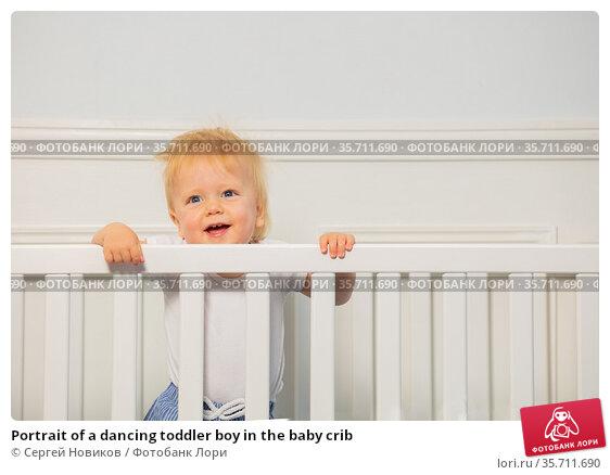 Portrait of a dancing toddler boy in the baby crib. Стоковое фото, фотограф Сергей Новиков / Фотобанк Лори
