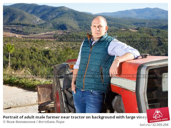 Portrait of adult male farmer near tractor on background with large vineyard. Стоковое фото, фотограф Яков Филимонов / Фотобанк Лори