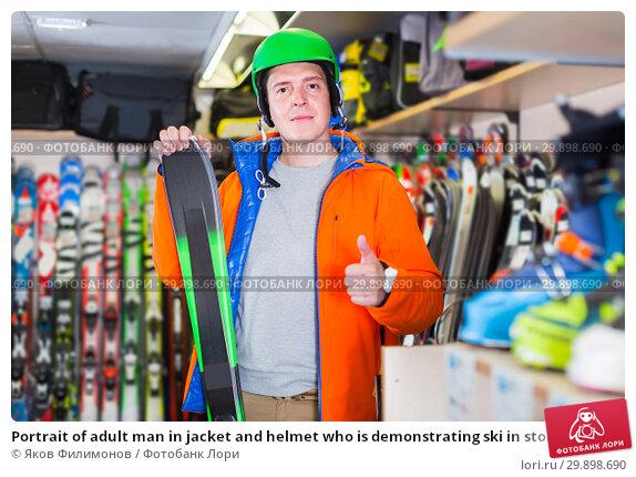 Купить «Portrait of adult man in jacket and helmet who is demonstrating ski in store.», фото № 29898690, снято 31 июля 2017 г. (c) Яков Филимонов / Фотобанк Лори
