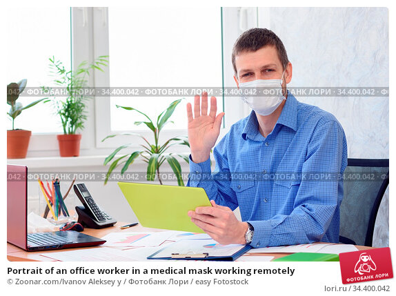Portrait of an office worker in a medical mask working remotely. Стоковое фото, фотограф Zoonar.com/Ivanov Aleksey y / easy Fotostock / Фотобанк Лори