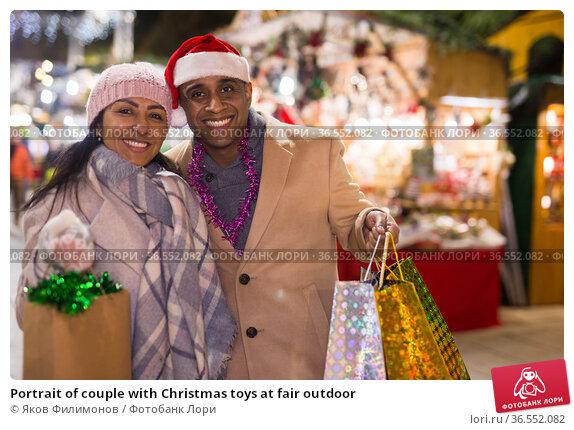Portrait of couple with Christmas toys at fair outdoor. Стоковое фото, фотограф Яков Филимонов / Фотобанк Лори