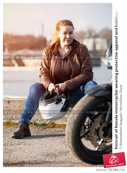 Portrait of female motorcyclist wearing protective apparel and holding crash helmet in hands, woman sitting on curb of roadside. Стоковое фото, фотограф Кекяляйнен Андрей / Фотобанк Лори