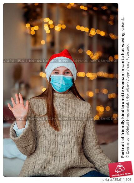 Portrait of friendly kind brunette woman in santa hat waving raised... Стоковое фото, фотограф Zoonar.com/Oleksii Hrecheniuk / easy Fotostock / Фотобанк Лори
