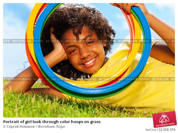 Portrait of girl look through color hoops on grass. Стоковое фото, фотограф Сергей Новиков / Фотобанк Лори